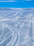 Groomed ski slope with several tracks. Empty morning ski slope groomed with several tracks from skiers and blue sky Stock Image