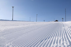 Groomed to manchester. A newly groomed skislope under a clear blue sky Stock Photos
