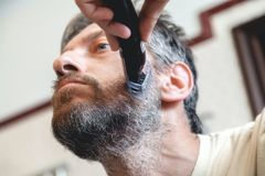 Grooming beard. Man alone strizhёt beard in bathroom. Grooming a beard trimmer. A nice gentleman in a beige T-shirt yourself shear his gray beard using a royalty free stock photos