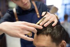 Male hairdresser cutting hair at barbershop. Grooming, hairdressing and people concept - close up of male client and hairdresser with comb and scissors cutting stock images