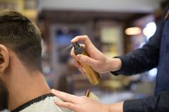 Barber applying styling spray to male hair at shop. Grooming, hairdressing and people concept - hairstylist applying styling spray to male client`s hair at stock photos