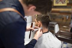 Male client and barber with trimmer cutting hair. Grooming, hairstyle and people concept - male client and barber or hairdresser with trimmer cutting hair at stock image