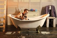 Grooming, hygiene, health. Skincare, treatment, therapy. Macho with shaving soap on beard hair look in mirror. Bearded man shave with razor in bath in bathroom stock photos