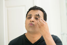 Grooming man. Closeup portrait, young handsome egotistical man in black t-shirt looking at mirror showing kisses and duck face, combing eyebrows admiring his stock images