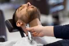 Man and barber with trimmer cutting beard at salon. Grooming and people concept - man and barber with trimmer or shaver cutting beard at barbershop royalty free stock image