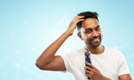 Smiling indian man with trimmer touching his hair. Grooming and people concept - smiling young indian man with trimmer touching his hair over grey background stock images
