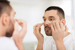 Young man applying cream to face at bathroom royalty free stock image