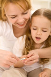 Grooming theme - woman cuts little girls nails Stock Images