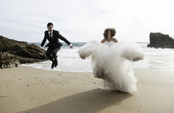 Grooms jumping beach Stock Photography