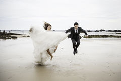 Grooms jumping beach Royalty Free Stock Images