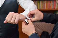 Grooms man helps the groom to put on black cufflinks on white sl Stock Image