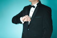 Grooms morning preparation, handsome groom getting dressed and preparing for the wedding, in black suit Royalty Free Stock Images