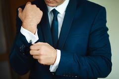 Grooms morning preparation, handsome groom getting dressed and preparing for the wedding, in dark blue suit Royalty Free Stock Photography
