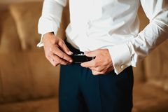 Grooms morning preparation, handsome groom getting dressed and preparing for the wedding, wearing a belt Stock Photography