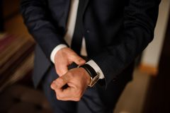 Grooms morning preparation. Handsome groom getting dressed in wedding suit Royalty Free Stock Photos