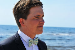 The Grooms ponders over the Future. A portrait of the groom by the sea pondering about what the future will bring. He has dark hair and brown eyes stock photo
