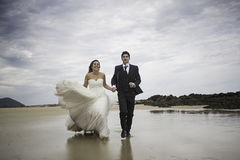 Grooms running beach. Marriage bridal dresses beach couple in love Royalty Free Stock Photography