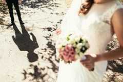 Grooms shadow nearly bride with wedding bouquet Royalty Free Stock Photo
