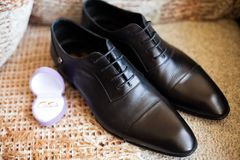 Grooms shoes. And wedding rings Stock Photo