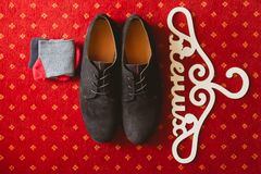The grooms shoes and socks. On the carpet. The word groom in Russian on a hanger Stock Image