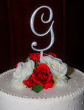 Grooms Wedding Cake. A white wedding cake decorated with red and white roses and a decorative G on black background Royalty Free Stock Images