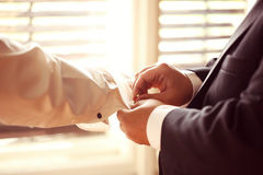 Groomsman aidant le marié photo stock
