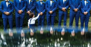 The groomsman in blue suits stand in a row.  royalty free stock photos