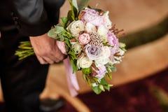 Groomsman boeketten van greep in hand jne voor bruidsmeisjes stock afbeelding