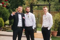 Stylish groomsman with groom standing on the backyard and prepare for the wedding ceremony. Friend spend time together. Groomsman with groom standing on the stock photography