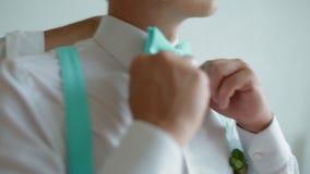 Groomsman helping groom with his suit stock footage