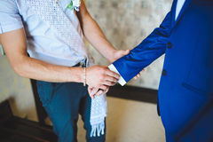 Groomsman Helping Groom with Sleeve Royalty Free Stock Images