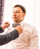 Groomsman helping groom to put on bow tie.  stock photos
