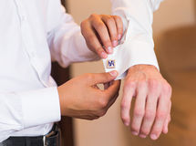 Groomsman helps groom to put on cufflinks close-up. Groomsman helps to groom to put on cufflinks royalty free stock photos