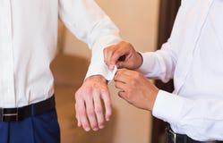 Groomsman helps groom to put on cufflinks close-up. Groomsman helps to groom to put on cufflinks royalty free stock photo