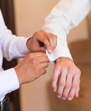 Groomsman helps groom to put on cufflinks close-up. Groomsman helps to groom to put on cufflinks royalty free stock images