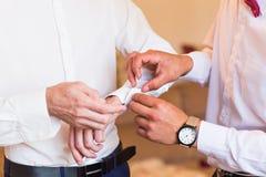 Groomsman helps groom to put on cufflinks close-up. Groomsman helps to groom to put on cufflinks royalty free stock image