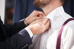 Groomsman helps to groom to put on shirt. Stock Images