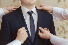 Groomsman helps to the groom. Groomsman helps to wear a jacket to the groom in room. Shallow depth of field royalty free stock image