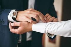 Groomsman helps to groom on wedding day. Groomsman helps to groom to put on cufflinks stock photography