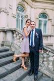 Groomsman posant avec la demoiselle d'honneur mignonne sur les escaliers du bâtiment autrichien classique photographie stock