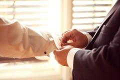 Groomsman som hjälper brudgummen arkivfoto