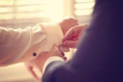 Groomsman som hjälper brudgummen arkivbilder