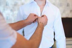 Groomsman som knäppas brudgums skjorta royaltyfria foton