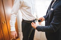 Groomsman som knäpper fast brudgums bälte royaltyfria foton