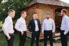 Groomsman spend time with groom at the backyard. Guys laugh and have fun.  stock image