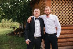 Groomsman spend time with groom at the backyard. Guys laugh and have fun.  royalty free stock photography