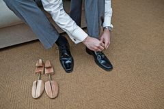 A groomsman ties up his new shoes beside a pair of shoe stretchers stock photo