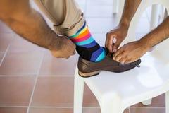 Groomsman helping groom. Groomsman tying shoelaces of the grooms shoes with colorful socks stock image