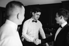 Groomsmen à moda que ajudam o noivo feliz que prepara-se na manhã Imagens de Stock Royalty Free