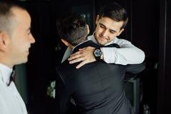 Groomsmen à moda que ajudam o noivo feliz que prepara-se na manhã para a cerimônia de casamento Foto de Stock